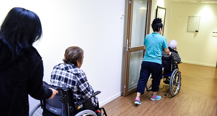 Personal hjälper gamla som sitter i rullstol på ett äldreboende.