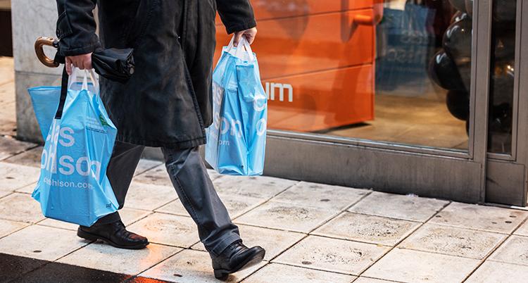 En man går med två kassar. Bara benen syns på bilden