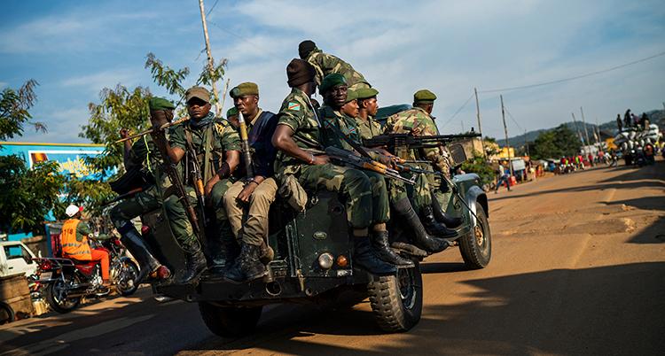 Många soldater i uniformen och vapen trängs på en ljeep