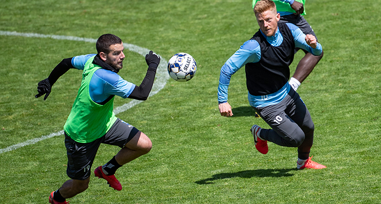 Två spelare i träningskläder jagar efter en boll
