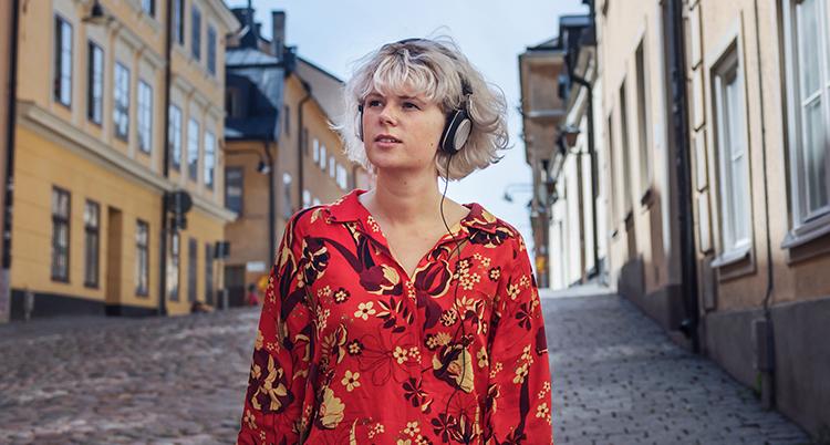En kvinna går på en gata med hörlurar på sig.