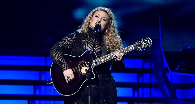 Hon håller i en gitarr.