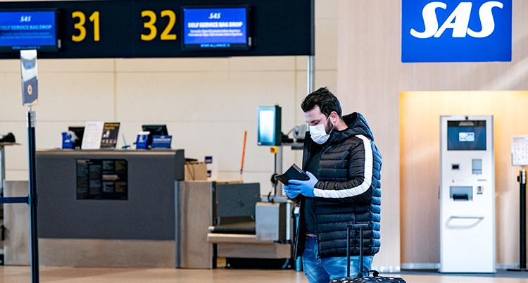 En man med munskydd står vid SAS disk på Arlanda. Han tittar ner i en bok