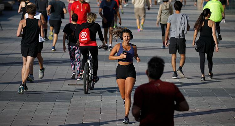 En kvinna kommer springande. Runt henne går många människor.