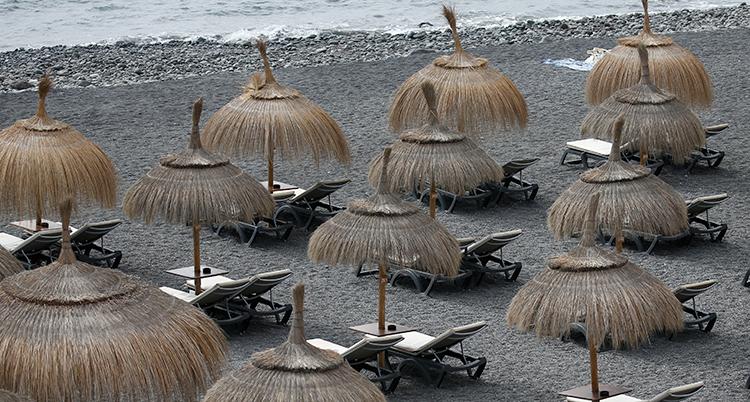 En strand med parasoller i bast och tomma solstolar
