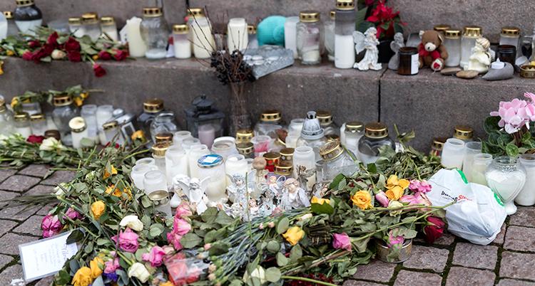 Blommor och ljus står på gatan.