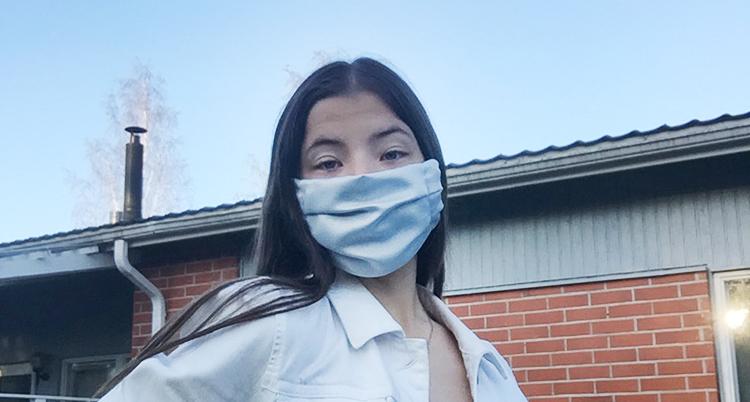 Hon har ett munskydd på sig.