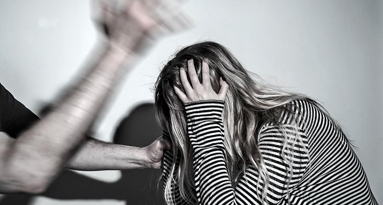 Bilden visar en man som slår en kvinna.
