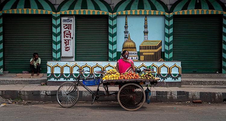 En kvinna står bakom en vagn med frukt. Hon har munskydd.