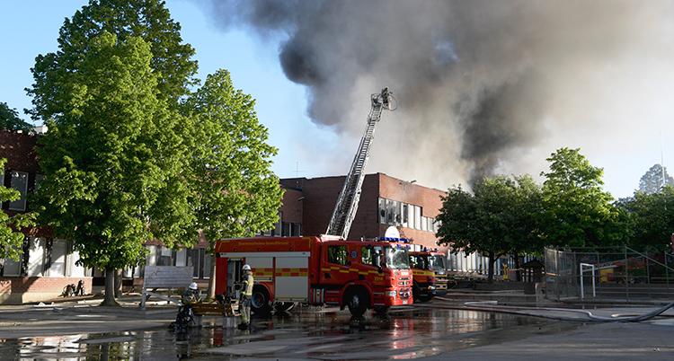 En bild på skolan från håll. Framför skolan står en brandbil med hissad stege över taket på skolan. Rök syns stiga upp mot himlen.