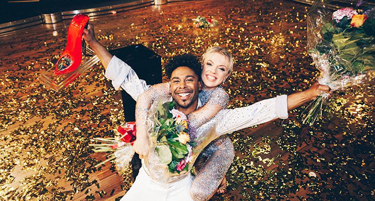 De två dansarna har vita kläder och är väldigt glada.