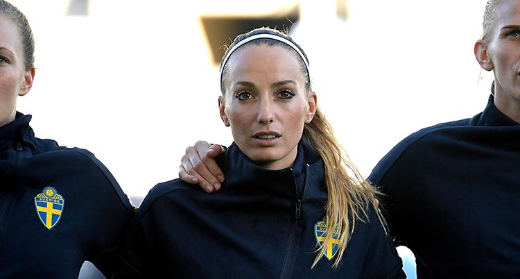 Bilden är innan en match med Sveriges landslag. Spelarna står med armarna om varandras axlar. I mitten av bilden står Kosovare Asllani.