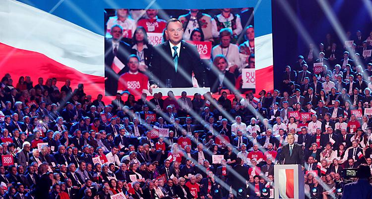 Bilden är tagen inomhus, i en stor lokal. En man står och pratar i en talarstol. Runtom sitter det en massa människor. De har skyltar och tröjor med hans namn på.