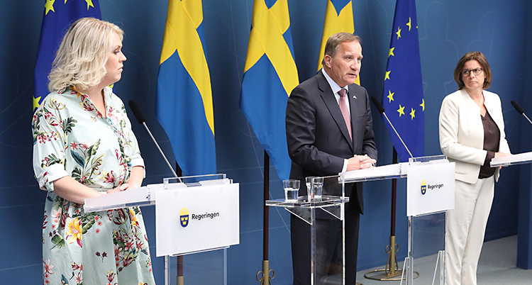 Tre politiker står på en scen. De pratar i mikrofoner. I bakgrunden finns svenska flaggor och EUs flagga.