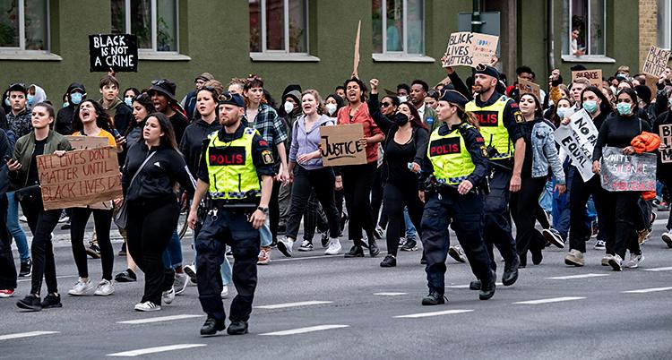 Många människor går på en gata. De har skyltar där det står saker. Vid sidan av dem går några poliser.