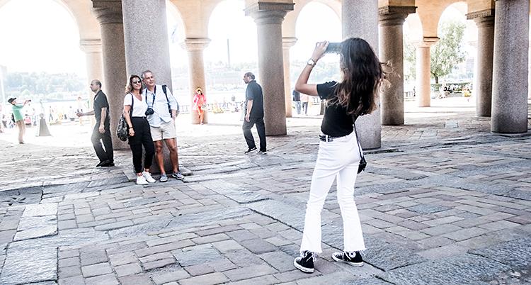 Bilden är tagen vid stadshuset i Stockholm. Två personer står vid en pelare. En tredje person tar en bild på dem med sin mobiltelefon.