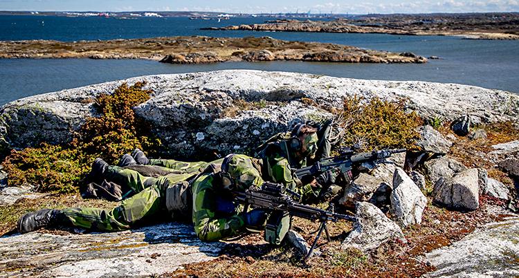 Bilden är från skärgården i Göteborg. Två män ligger på en klippa. De har gröna kläder och vapen.
