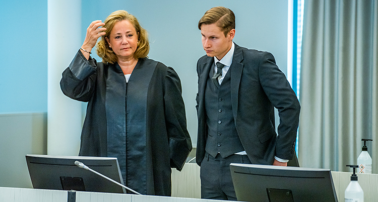 Två personer står i ett rum i en domstol. Kvinnan står till vänster. Mannen står till höger. De har fina kläder på sig.