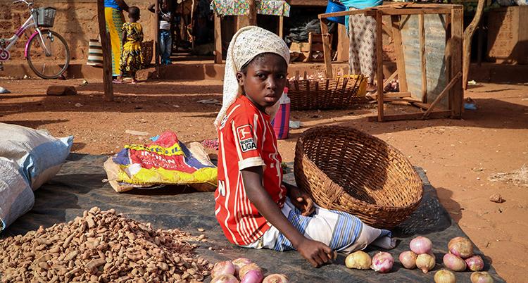 Ett barn sitter på en marknad med en korg i knäet.