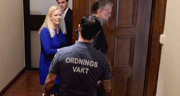 En ordningsvakt tittar på Anna Linstedt när hon går in genom en dörr.