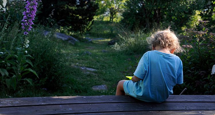 Ryggen på ett barn syns. Det är gräs och blommor framför barnet.