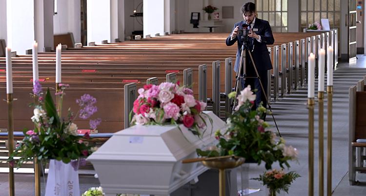 Han filmar en begravning en kista i en kyrka.