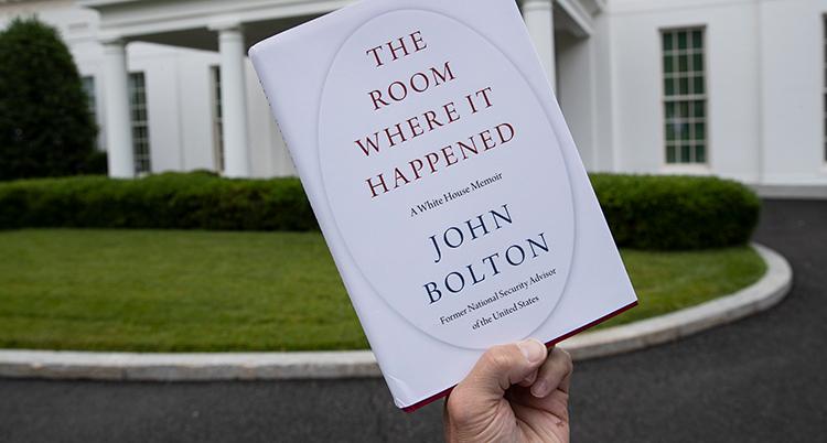 En hand håller upp en bok. I bakgrunden är presidentens hus.