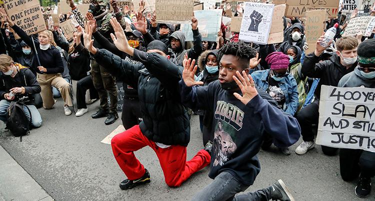 Flera människor står på knä och sträcker upp händerna. Emn del har skyltar med protester.
