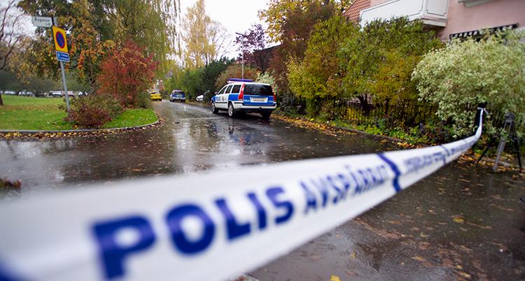 En polisbil står på en gata som är våt av regn. Det är buskar och låga hus. Längst fram på bilden är ett band där det står Polis. Det spärrar gatan.