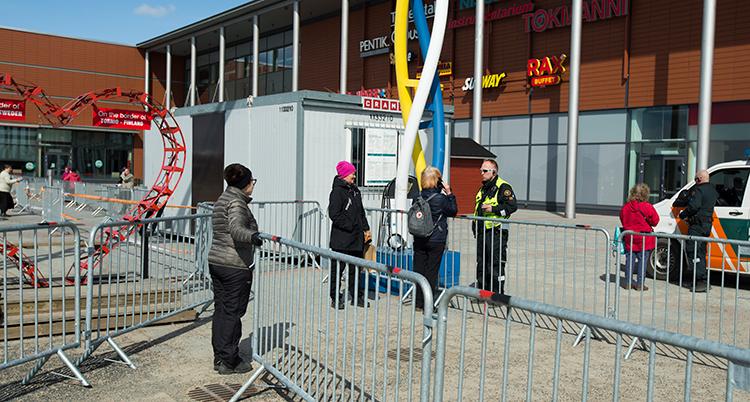 Ett staket har satts upp vid gränsen till Finland i Haparanda. Några människor står och pratar.
