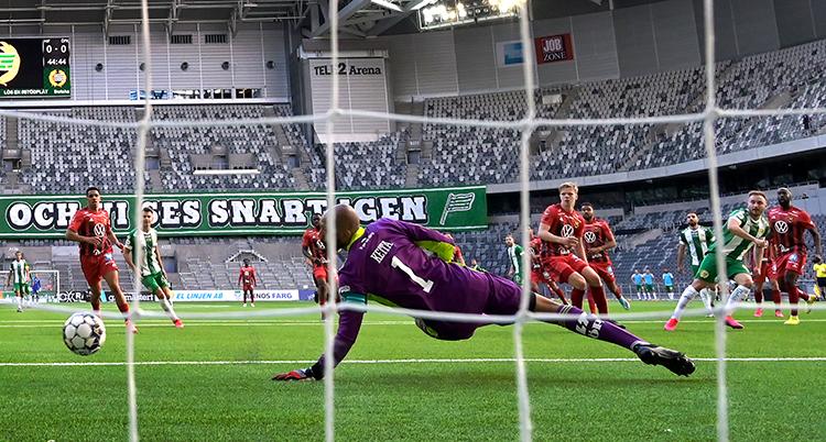 Bilden är tagen från baksidan av målet. Måvakten släcker sig efter boll som är på väg mot mål. Spelarna tittar på bollen. Bakom dem är tomma läktare.