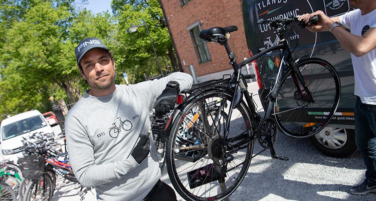 En man vid en cykel som står på en ställning. Han håller på att laga den.