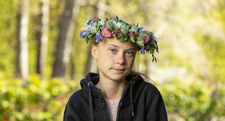 En bild på Greta Thunberg med blomsterkrans i håret.