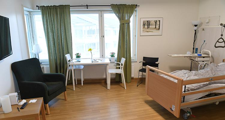 I rummet syns en säng, ett bord och en fåtölj.
