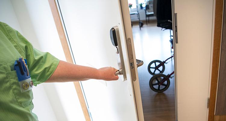 En sköterska öppnar en dörr på ett hem för gamla.