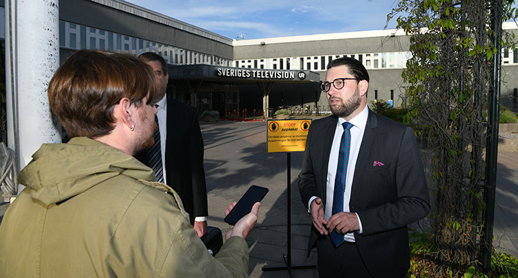 Jimmmie Åkesson framför SVTs entré blir intervjuad av en journalist med mikrofon.