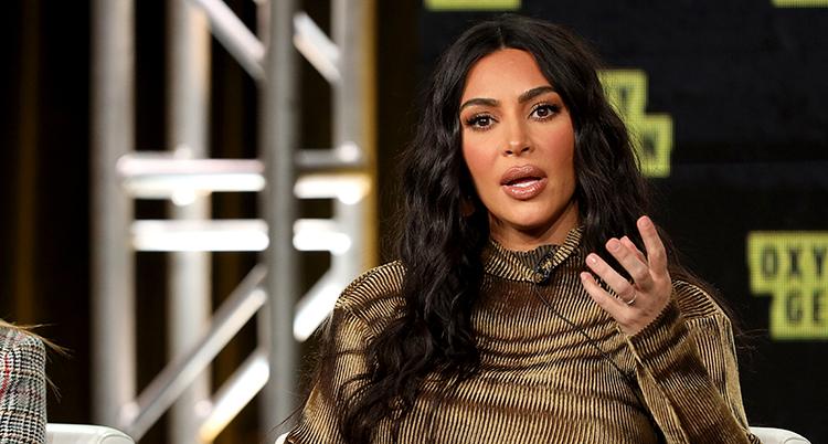 Kim pratar. Hon ser allvarligt ut och lyfter ena handen i en gest.
