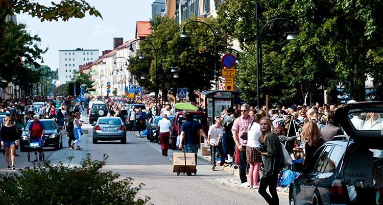 Många människor går längs en gata.