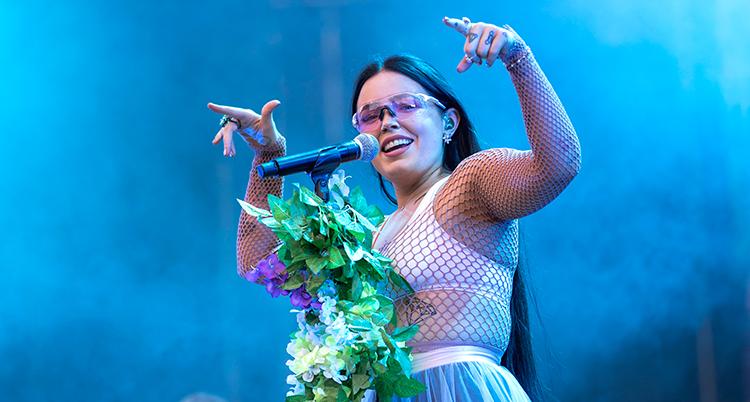 Hon står på en scen och sjunger.