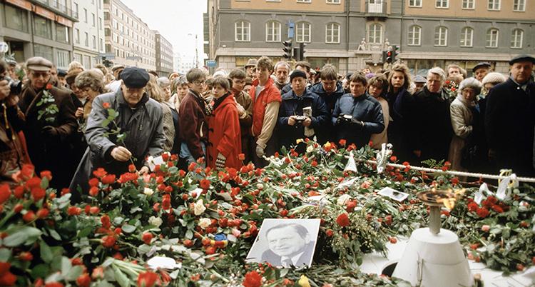 Många människor står runt en stor hög men blommor. En man böjer sig fram och lägger ner en röd ros.