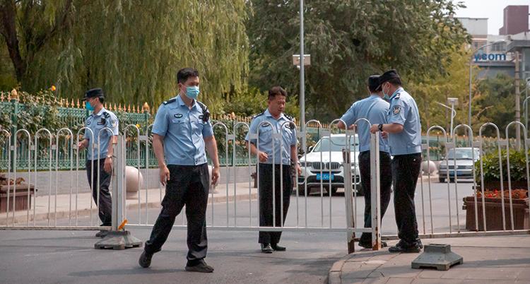 Flera poliser i blå kläder står vid ett staket.