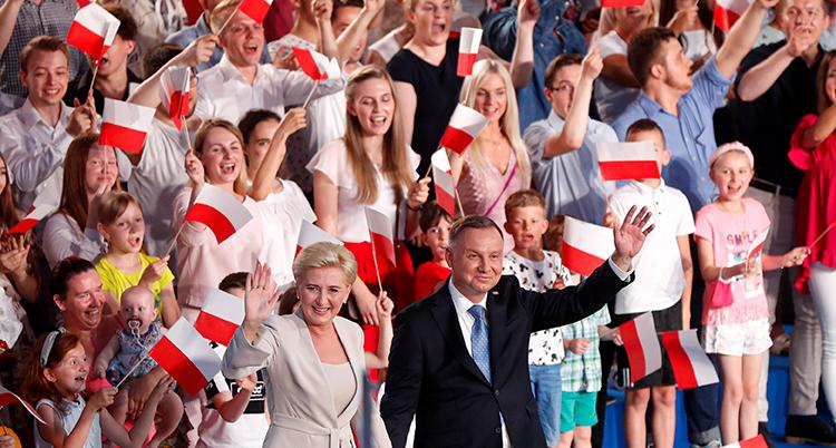 En massa människor med polska flaggor. Framför den stor presidenten och hans fru och vinkar.