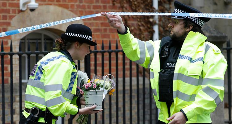 En polis bär på blommor.
