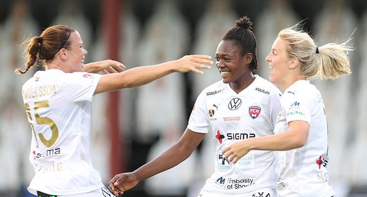 Tre spelare ser glada ut. De firar ett mål och ska precis krama varandra.