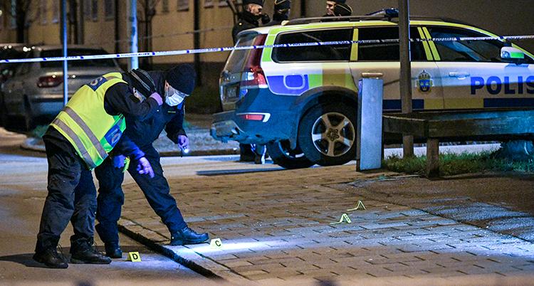 Två poliser undersöker marken. En polisbil står bredvid.