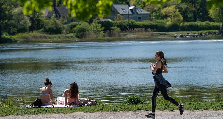 En kvinna springer i naturen. I bakgrunden syns grönska och vatten.