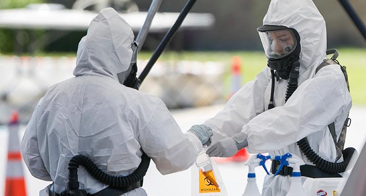 Två personer har skyddskläder och masker för ansiktet.