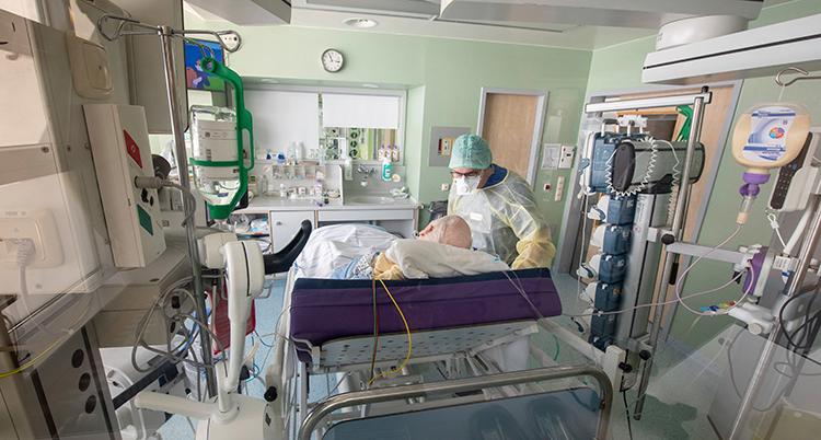 Läkaren har skydd för munnen. Patienten ligger i en säng.