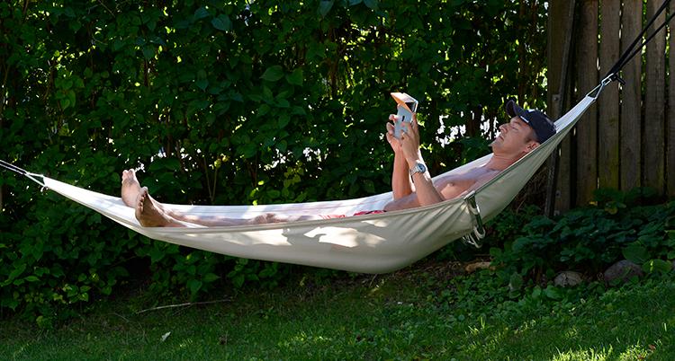 En man ligger i en hängmatta. Han ligger i skuggan.