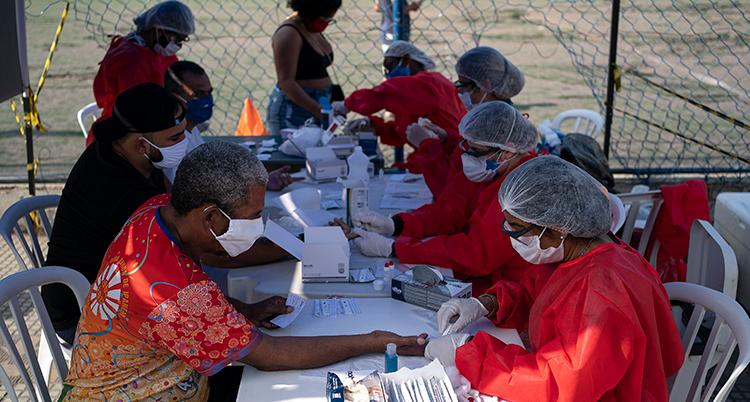 Vårdpersonal i munskydd och röda kläder tar blodprover från personer med munskydd vid ett långt bord utomhus.